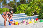 picture of girl toy  - Little girls playing with beach toys during tropical vacation - JPG