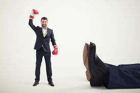 foto of knockout  - smiley winner businessman in red boxing gloves standing near big lying mans legs over light grey background - JPG