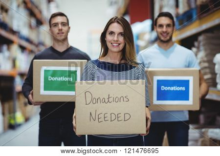 Volunteers smiling at camera holding donations boxes in a large warehouse