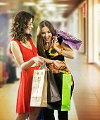 Two beautiful young women in a shopping center checking bags