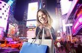 Постер, плакат: Улыбается женщина перевозящих некоторые сумки на улице города