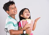 asian little boy and girl watching movie with pop corn, little indian girl sitting with brother watc poster