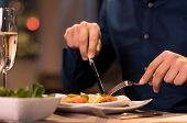 Close up of a male hands cutting and eating delicious salad with knife and fork at restaurant. Man e poster