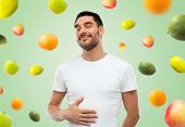 Постер, плакат: food healthy eating diet and people concept happy full man touching his tummy over green backgro
