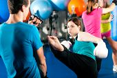 stock photo of sandbag  - Woman Kick boxer kicking her trainer in a sparring session - JPG