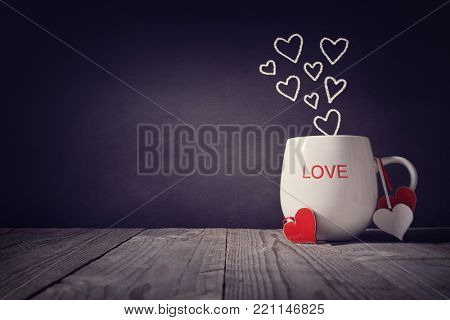 poster of Love written on a mug with hearts concept for Valentines day or Mothers day background with copy spa