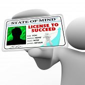 A person holds a badge holding a laminated pass reading License to Succeed, illustrating the drive a