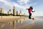 image of beach-house  - young adult woman jumping in front of her beach apartment - JPG
