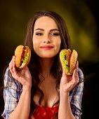 Woman eating hamburger.Day of discounts. One hamburger as sale gift. Student consume fast food. Girl poster