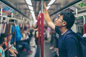 Young Man Traveler Is Visiting At Hongkong By Subway Mtr Train. The Mass Transit Railway Is The Rapi poster