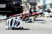 Close-up of a bicycling helmet fallen on the asphalt  next to a bicycle after car accident on the st poster