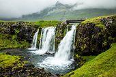 At the foot of the mountain Kirkjoufell powerful waterfalls Kirkjoufellfoss. Overcast summer day in  poster