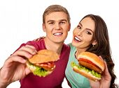 Couple eating fast food. Man and woman eat hamburger with ham. Friends holding two burder junk on wh poster