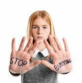 Teenage girl with words Stop bullying on her hands against white background poster