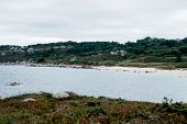 Beautiful empty beach in overcast weather. Seascape with rocky coastline and greeen trees, Galicia,  poster