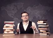A young ambitious geography teacher in glasses sitting at classroom desk with pile of books in front poster