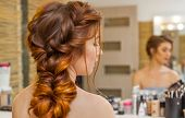 Beautiful, With Long, Red-haired Hairy Girl, Hairdresser Weaves A French Braid, In A Beauty Salon. P poster