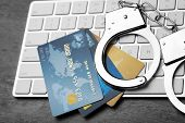 Credit cards and handcuffs on computer keyboard, closeup poster