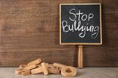 Chalkboard with text Stop bullying on wooden background poster