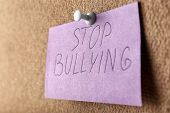 Note with text Stop bullying pinned to board poster