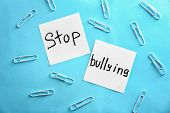 Notes with text Stop bullying on color background poster