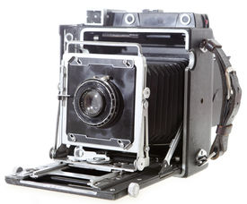 """foto of workhorses  - A fully working 4x5 American press camera probably c.1958 with a 1920s lens isolated on white. This was the workhorse for a generation of US pressmen. NB: Anastigmat on the lens simply means """"corrected for astigmatism"""" it is not company specific - JPG"""