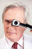 Eye doctor optometrist with opthalmoscope.