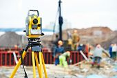 image of geodesic  - Surveying measuring equipment theodolite transit on tripod at construction building area site - JPG