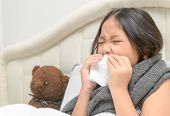 Sick Child. Asian Little Girl Has Runny Nose And Blows Nose Into Tissue Lying With Her Bear On Bed,  poster
