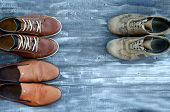 On A Wooden Background Are Three Pairs Of Brown Shoes. One Pair Of Leather Sneakers Is Very Worn, Th poster