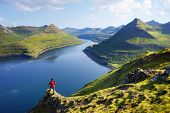 View on Funningur fjord from the Funningur top. Eysturoy Island, Faroe islands. Tourist in a red jac poster
