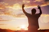 Silhouette of a man with hands raised in the sunset concept for religion, worship, prayer and praise poster