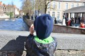A Boy With A Smartphone In His Hands Takes A Photo Of A Historical Landmark In Belgium, Bruges. Excu poster