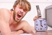 Man Bearded Annoyed Sleepy Face Lay Pillow Near Alarm Clock. Break Discipline Regime. Stop Ringing.  poster