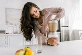 Attractive Pregnant Woman Preparing Tasty Smoothie In Blender poster
