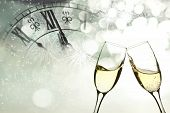 image of flute  - Glasses with champagne against fireworks and clock close to midnight  - JPG