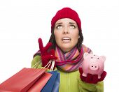 Stressed Mixed Race Woman Wearing Winter Clothing Looking Up Holding Shopping Bags and Piggy Bank Is
