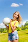 stock photo of 13 year old  - Cute and happy 13 years old girl with long blond hair standing in the grass with the ball in the park on sunny summer day - JPG