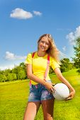 picture of 13 year old  - Happy and smiling 13 years old girl with long blond hair standing in the grass with the ball in the park on sunny summer day - JPG