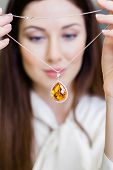 Girl holding necklace with yellow sapphire at jeweler's shop. Concept of wealth and luxurious life