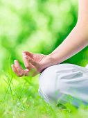 Close up of female hand zen gesturing. Woman sits in asana position. Concept of healthy lifestyle an