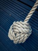 Nautical knot on a blue wooden background