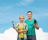 repair, construction and maintenance concept - smiling couple with hammer and drill over white backg