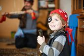 picture of pirates  - Little preschool boy of 4 years celebrating birthday in pirate costume indoors with father on background - JPG
