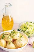 Fresh boiled potatoes with oil and salad