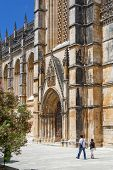 Batalha, Portugal - July 17, 2013: Locals passing by the South Portal of the Batalha Monastery. Mast