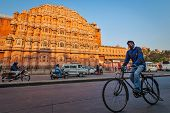 JAIPUR, INDIA - NOVEMBER 18, 2012: Unidentified Indian man driving bicycle in front of  Hawa Mahal p