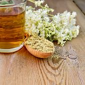 foto of meadowsweet  - Wooden spoon with dried flowers a bouquet of fresh flowers of meadowsweet tea in glass mug on the wooden boards - JPG