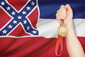 Medal In Hand With Flag On Background - State Of Mississippi. Part Of A Series.