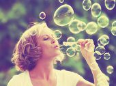 stock photo of bubbles  - a pretty girl blowing bubbles  - JPG